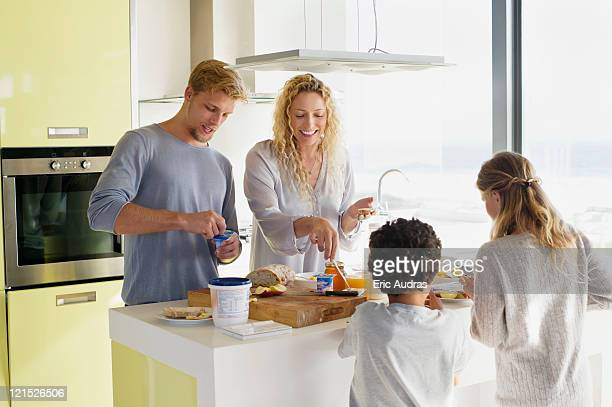 Couple with their two children preparing food at a domestic kitchen