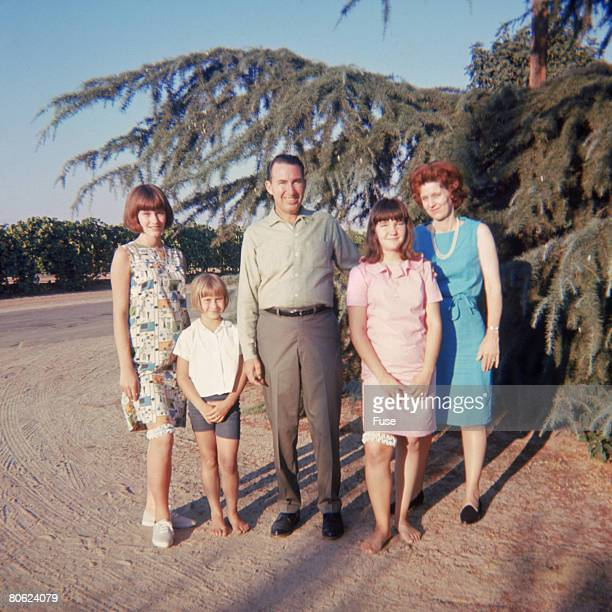 Couple with three children standing in yard