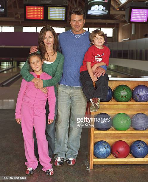 Couple with two children (3-8) in bowling alley, smiling, portrait