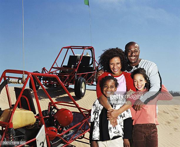 Couple with two children (8-10) standing beside dune buggies, portrait