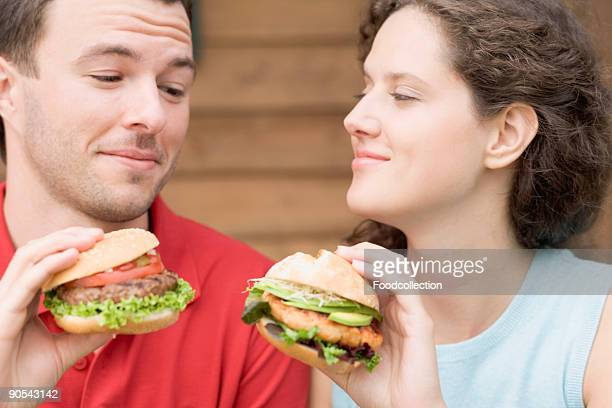 Couple with two different burgers, smiling
