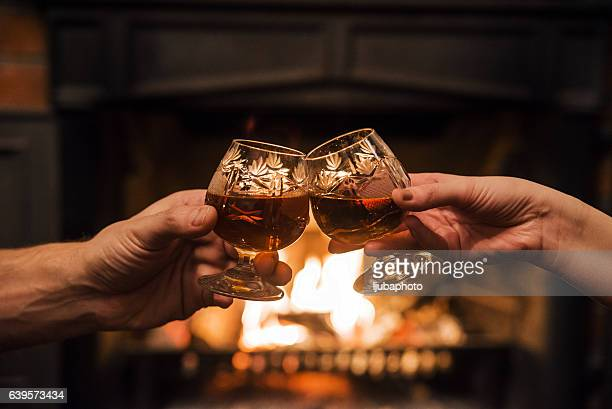 Couple with Two glasses of alcoholic drink  in front fireplace