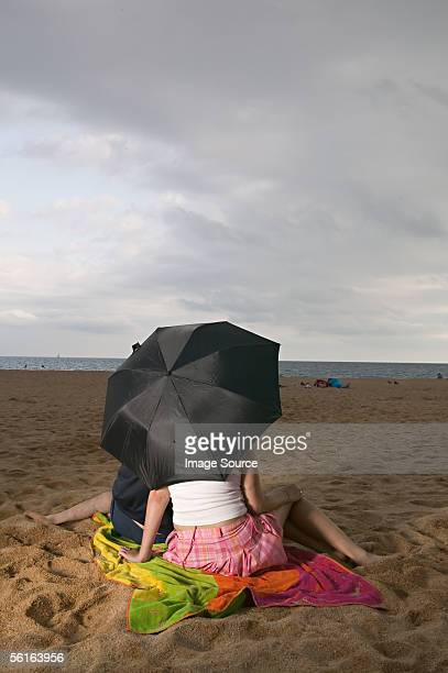 Couple with umbrella on beach