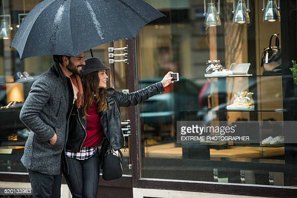 Couple with umbrella photographing the products in the store