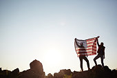 Wide shot image with copy space of backlit couple standing on mountain top against the sun and sky holding big USA banner up high