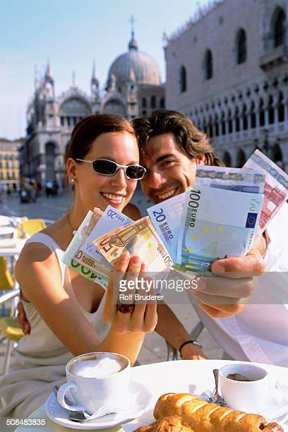 Couple with wads of cash having breakfast at cafe