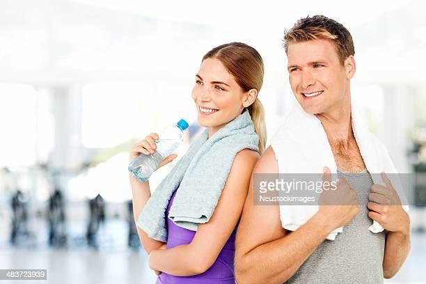 Casal com Garrafa de água e toalhas de olhar para longe no ginásio