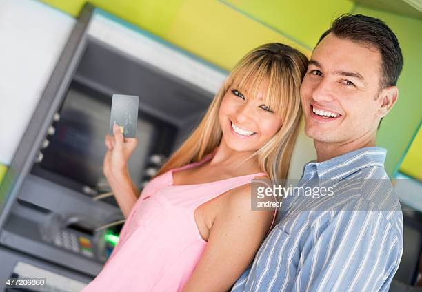 Couple withdrawing cash from an ATM