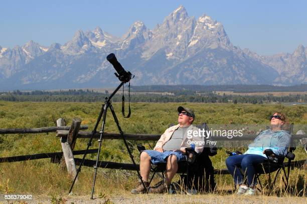 A couple woman views the solar eclipse in the first phase of a total eclipse in Grand Teton National Park on August 21 2017 outside Jackson Wyoming...