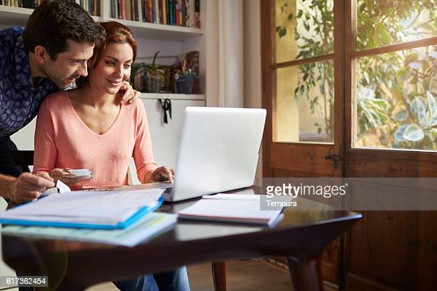 Couple working through taxes forms at home.