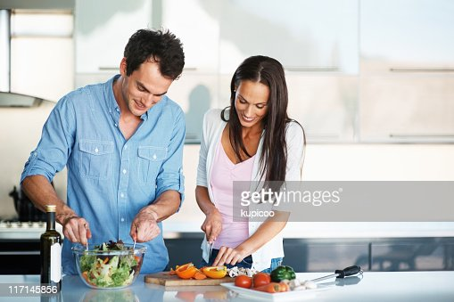 Couple working together in the kitchen : Stock Photo