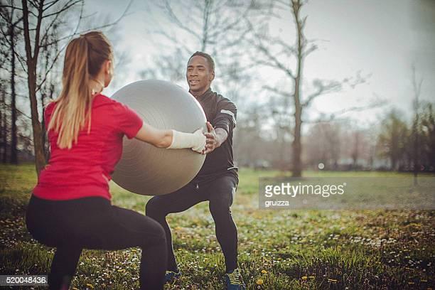 Paar Trainieren Sie mit fitness-ball zusammen in der Stadt Park