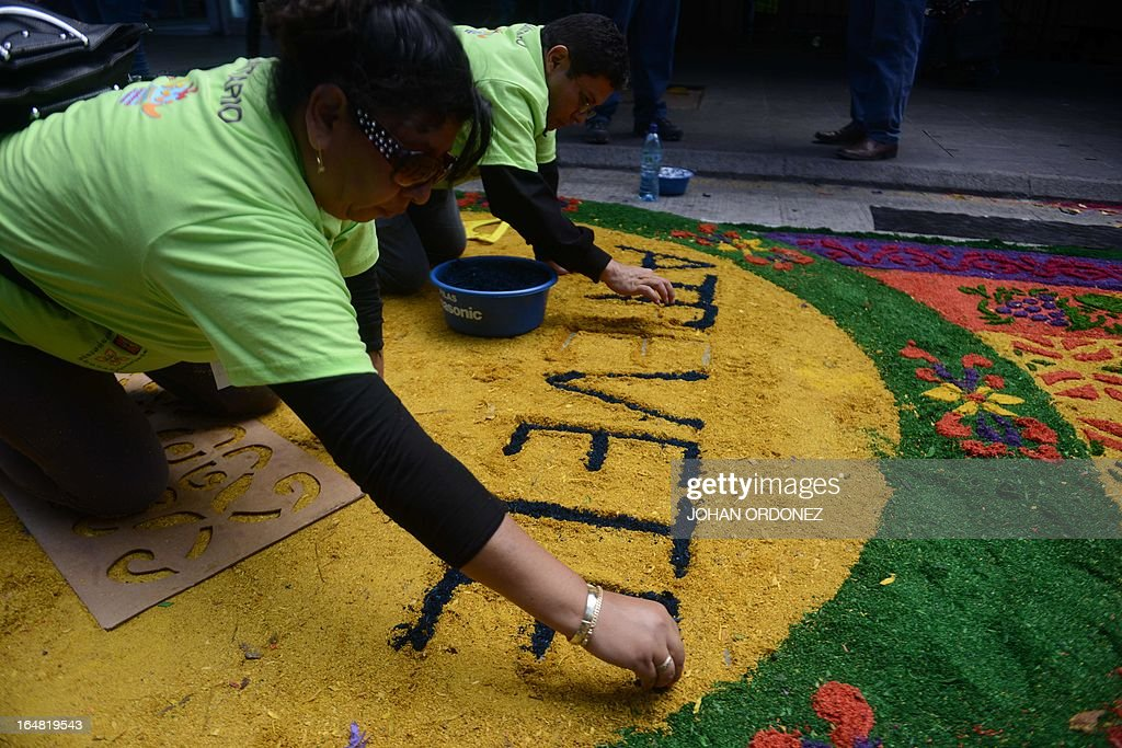 A couple works on the making of a 1,400 meters carpet of flowers and colored sawdust, carried out by municipal employees and volunteers in an attempt to set a Guinness World Record for the longest carpet of the world, in Guatemala City on March 28, 2013. These carpets are traditionally made during Hoy Week each year. AFP PHOTO / Johan ORDONEZ