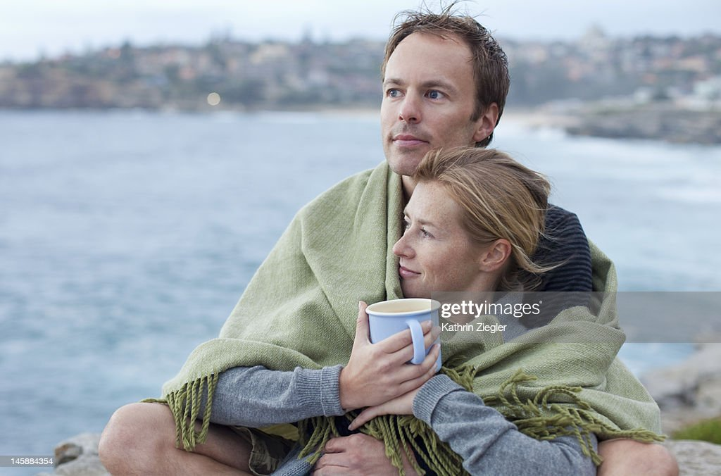 couple wrapped in a blanket, looking at the ocean : Stock Photo