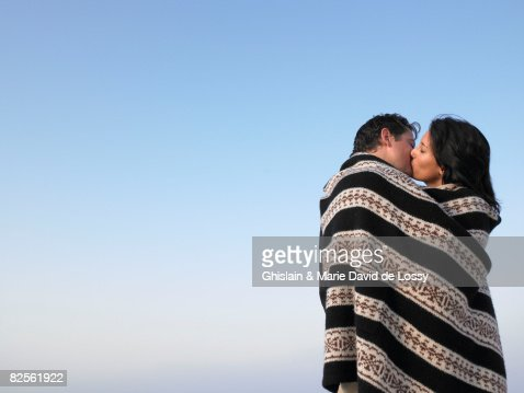 Couple wrapped in a cover, kissing : Stock Photo