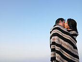 Couple wrapped in a cover, kissing