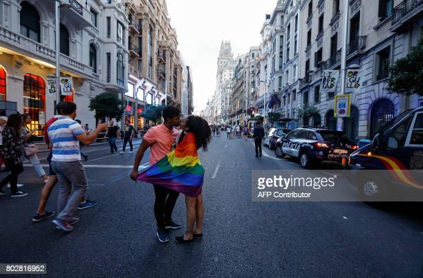 A couple wrapped in a rainbow flag kisses in Gran Via street after the 'Pregon' of the WorldPride 2017 in Madrid on June 28 2017 Thousands of...