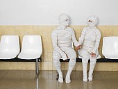 Couple wrapped in bandages holding hands