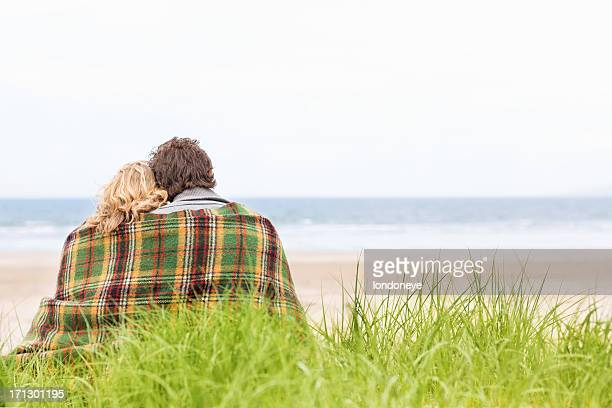 Couple Wrapped In Blanket At Beach