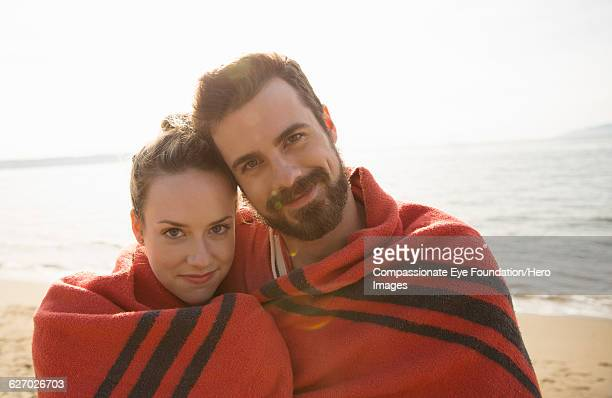 Couple wrapped in blanket hugging on beach