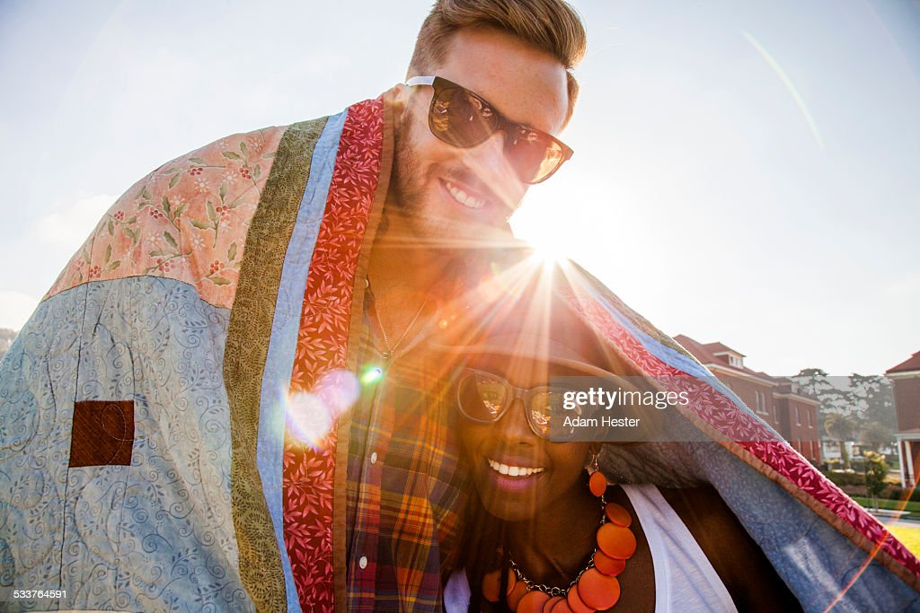 Couple wrapped in blanket smiling outdoors : Stock Photo