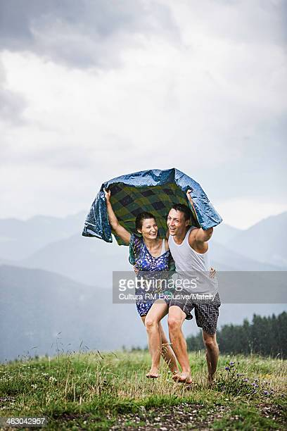 Couple wrapped in picnic blanket running for cover, Tyrol, Austria