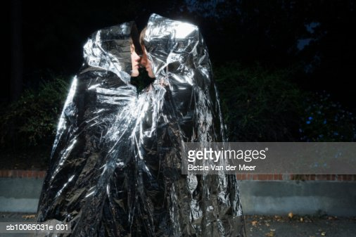 Couple wrapped in silver survival blanket, kissing : Stock Photo