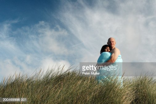 Couple wrapped in towel standing amongst long grass under cloudy sky : Stock Photo