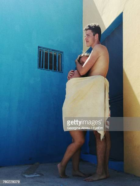 Couple Wrapped In Towel Standing By Wall