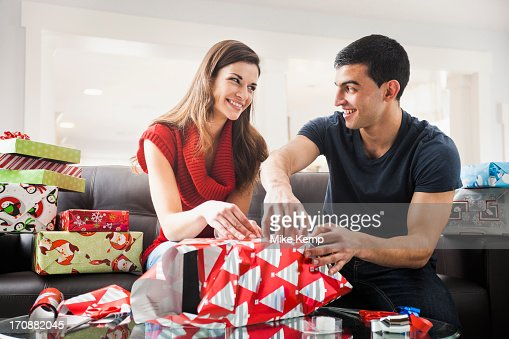 Couple wrapping Christmas presents in living room