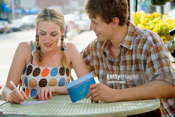 Couple writing postcards at outdoor cafe
