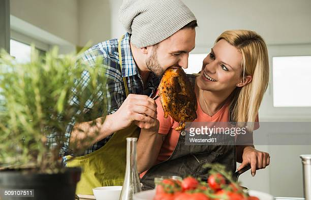 Coupleg in kitchen eating steak from frying pan