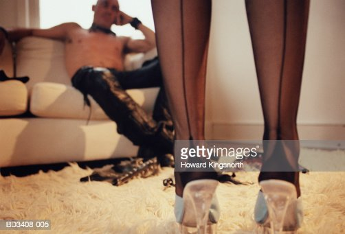 Couple,man sitting on sofa,fetish toys on floor,woman's legs in fore : Stock Photo