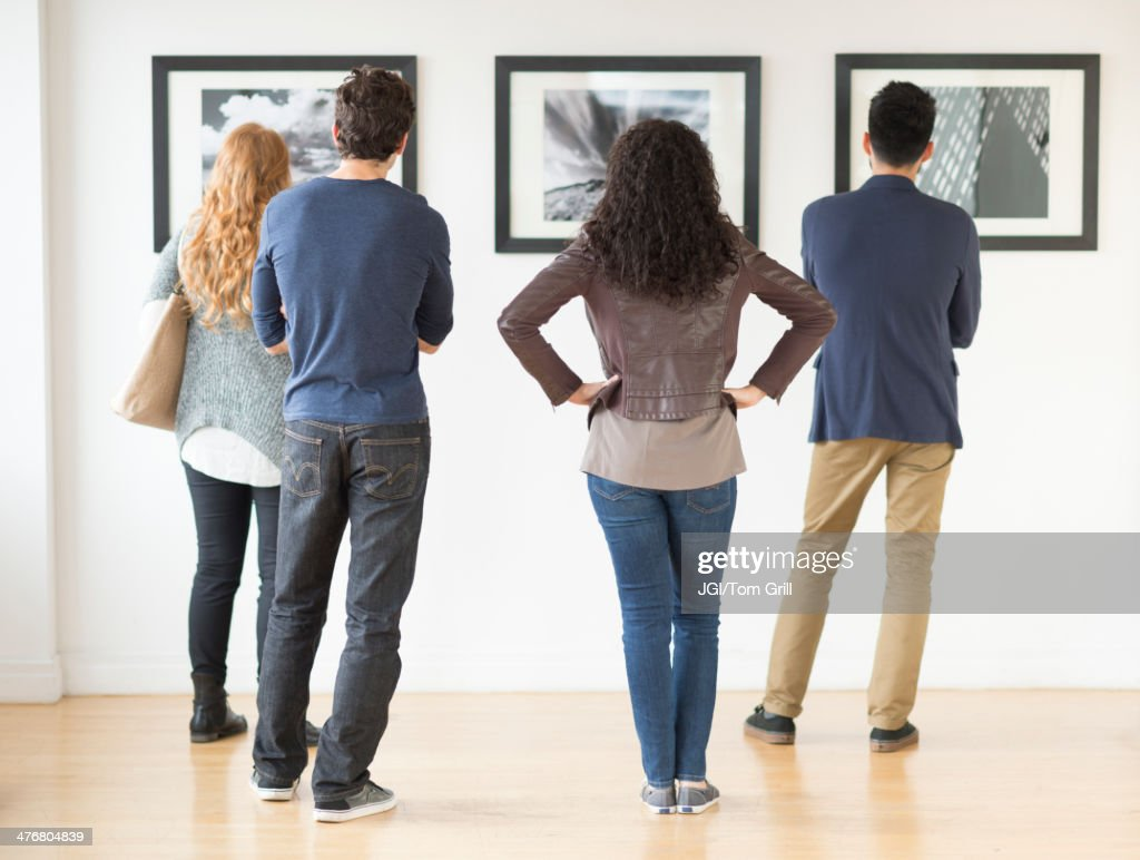 Couples admiring art in gallery : Stock Photo