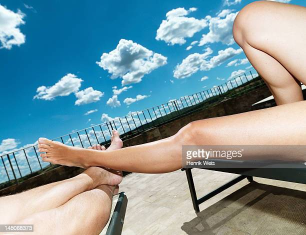 Couples bare legs on lawn chairs