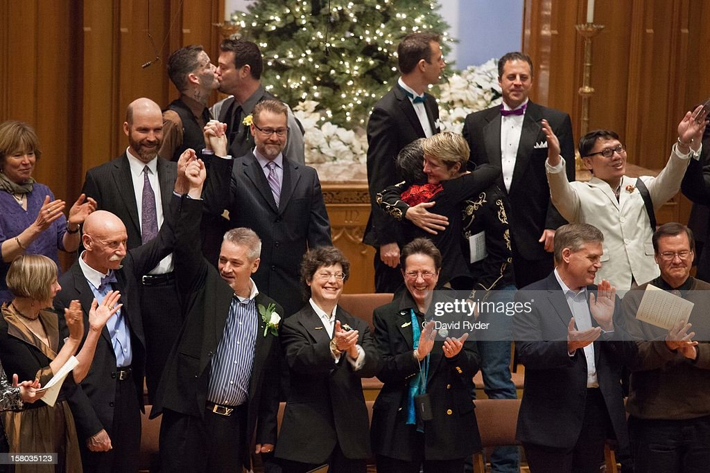Couples celebrate the completion of a mass wedding for 25 same-sex partners at Seattle First Baptist Church on December 9, 2012 in Seattle, Washington. Today is the first day that same-sex couples can legally wed in Washington state.