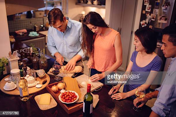 Couples chatting in a kitchen while dinner is being prepared