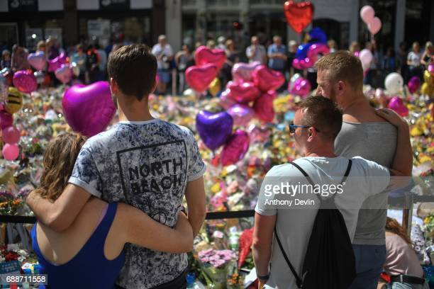 Couples comfort one another as flowers and balloons are left in Saint Ann's Square in tribute to those killed in an explosion at the Manchester Arena...