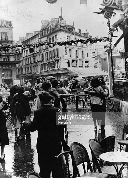 Couples dancing in a Paris caf on the 14th July celebrations despite the rain