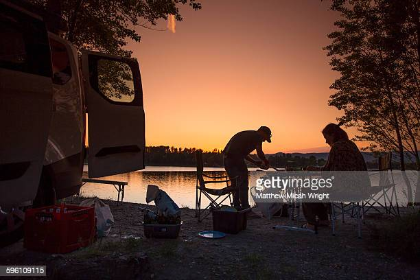 Couples enjoy a sunset from inside a camper.