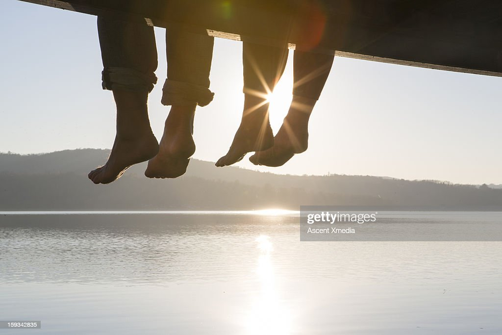 Couple's feet dangle from dock,above tranquil lake : Stock Photo
