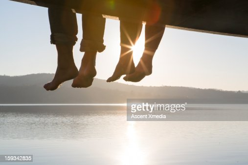 Couple's feet dangle from dock,above tranquil lake