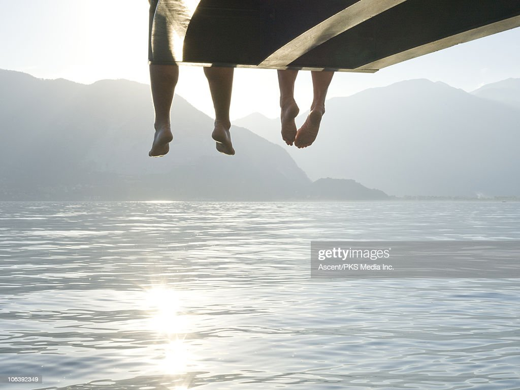Couple's feet dangle from end of lake wharf : Stock Photo