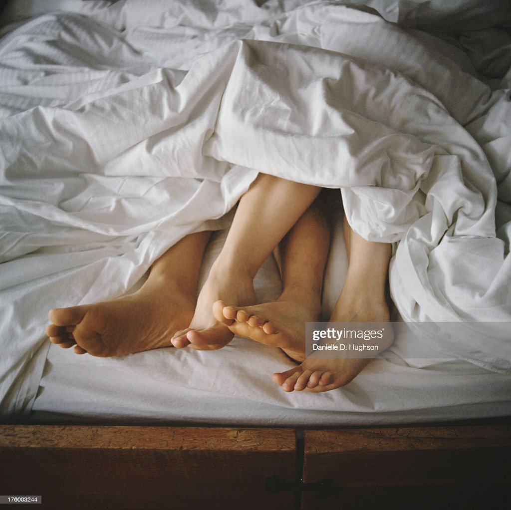 Couple's Feet Entangled in Bed