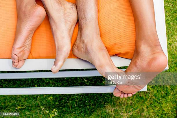 Couple's feet entwined on sunlounger