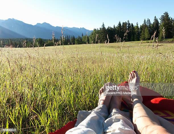 Couples' feet lying in blanket, in mountain meadow