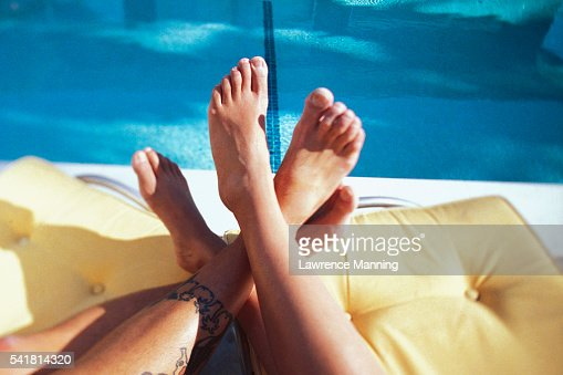 pool chairs couples feet on pool chairs stock photo getty images