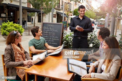 2 couples getting ready to order with waiter