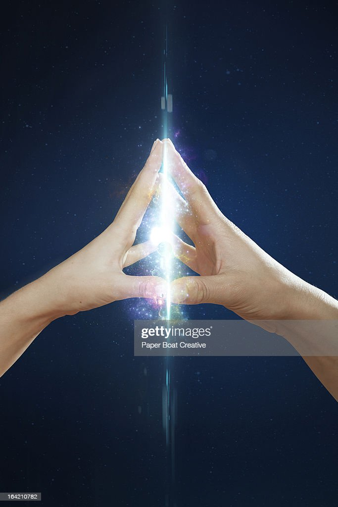 couples hands touching and creating a cosmic glow