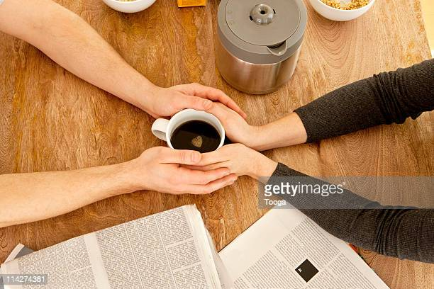 Couple's hands wrapped around one cup of coffee